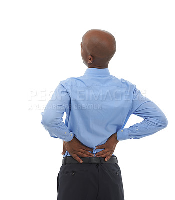 Buy stock photo Rearview studio shot of an african american businessman holding his lower back in pain