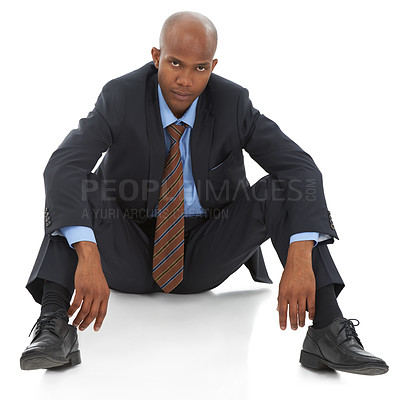 Buy stock photo A young African-American businessman sitting despondently against a white background
