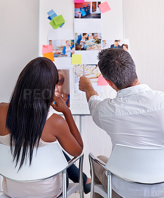 Buy stock photo Rearview shot of two colleagues looking at a design board together