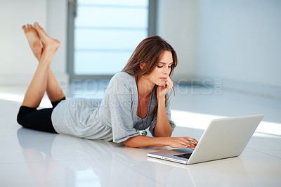 Buy stock photo Thoughtful young lady lying on floor using laptop