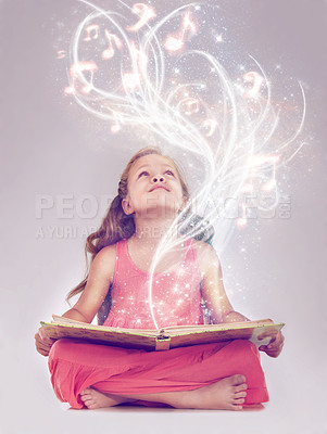 Buy stock photo Studio shot of a young girl reading a storybook