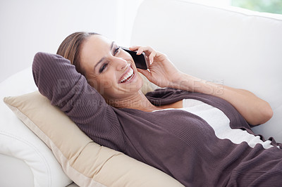 Buy stock photo A young woman lying on her couch speaking on her cellphone