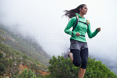 Buy stock photo A young woman sprinting along a mountain road on a crisp morning