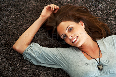 Buy stock photo Young woman lying on the floor and smiling