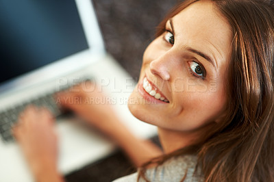 Buy stock photo Happy young woman relaxing with a laptop