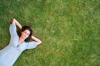 Buy stock photo An attractive young lady sleeping on green grass with loads of copyspace for your text