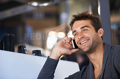 Buy stock photo A young man speaking on his cellphone while sitting in a coffee shop