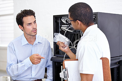 Buy stock photo One man holding a wire for the computer and getting in a disagreement with another business man