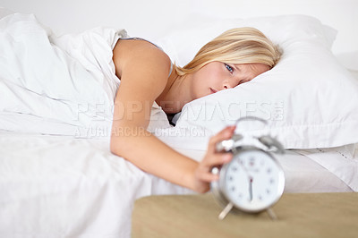 Buy stock photo A young woman putting her alarm clock off in the morning
