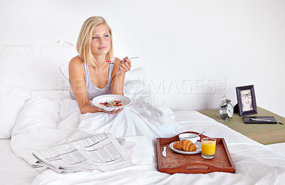 Buy stock photo A pretty young blond woman sitting in her bed enjoying a relaxing breakfast