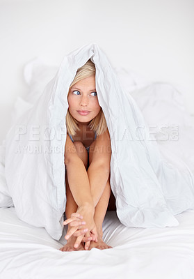 Buy stock photo Shot of an attractive young woman sitting on her bed and peeking out from under the covers