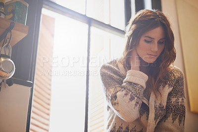 Buy stock photo Low angle shot of a beautiful young woman sitting by a window in a kitchen