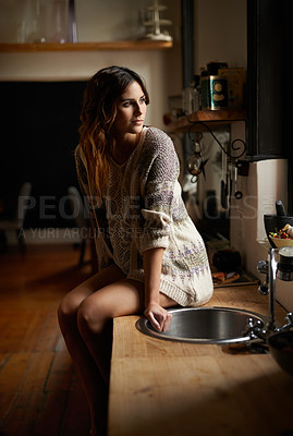 Buy stock photo Shot of a beautiful young woman sitting on the counter in a rustic kitchent