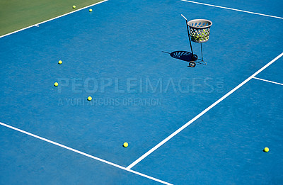 Buy stock photo A basket of balls standing on an empty tennis court