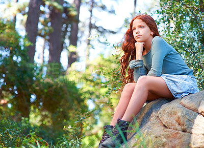 Buy stock photo Low-angle view of a young red-haired girl sitting on a boulder and looking into the distance
