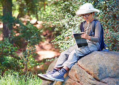 Buy stock photo A little boy with a book in his hand sitting on a rock