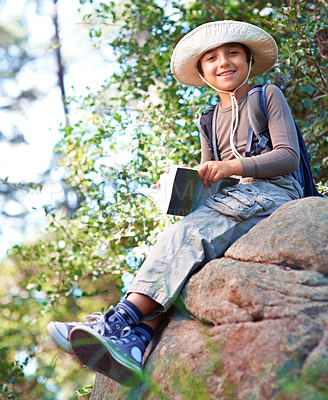 Buy stock photo Low-angle view of a little boy with a book in his hand sitting on a rock