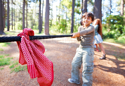 Buy stock photo Group of happy children playing a tug of war outdoors