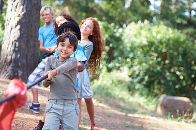 Buy stock photo Children playing at tug-of-war in the woods