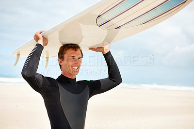 Buy stock photo Shot of a young surfer at the beach carrying his board on his head