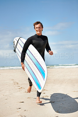Buy stock photo A handsome surfer running down the beach with his surfboard
