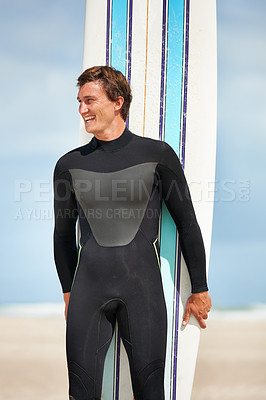 Buy stock photo Shot of a handsome surfer standing at the beach with his surfboard
