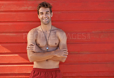 Buy stock photo A handsome lifeguard standing outside on the beach looking at the camera