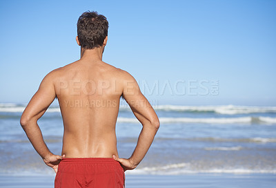 Buy stock photo Cropped rear view of a male lifeguard looking out at the ocean