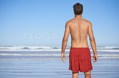 Buy stock photo Rear view of a male lifeguard looking out over the ocean