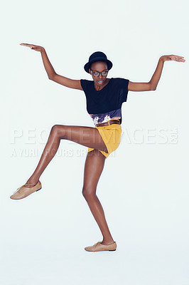 Buy stock photo Studio shot of a young ethnic hipster balancing on one leg with her arms raised