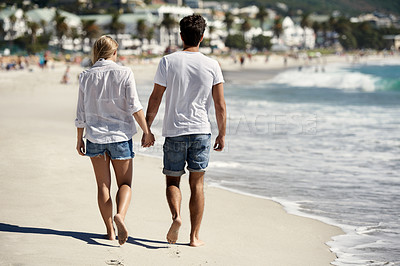 Buy stock photo A back view of a couple walking on the beach holding hands
