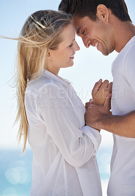Buy stock photo Shot of a young couple sharing an affectionate moment at the beach
