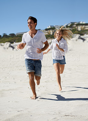 Buy stock photo A young couple running along the sand on the beach