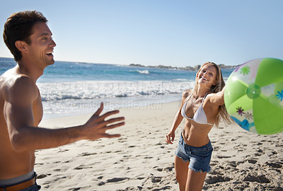 Buy stock photo A young couple playing with a beach ball