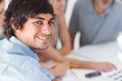 Buy stock photo A handsome young man sitting with his colleagues in the office boardroom