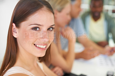 Buy stock photo A businesswoman smiling at the camera as her colleagues discuss something around a boardroom table