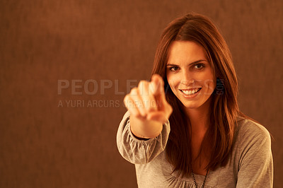 Buy stock photo An attractive young woman holding up a holly branch and blowing a kiss at the camera