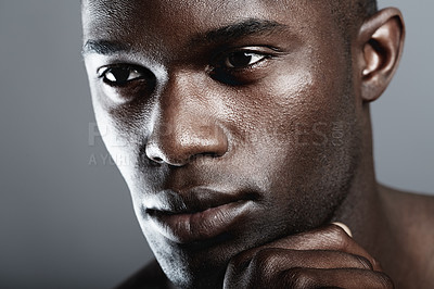 Buy stock photo A handsome african male looking thoughtful in studio