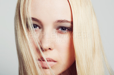 Buy stock photo Closeup portrait of a beautiful young blonde woman gazing intently into the camera