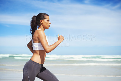 Buy stock photo Cropped shot of a young woman running along the beach