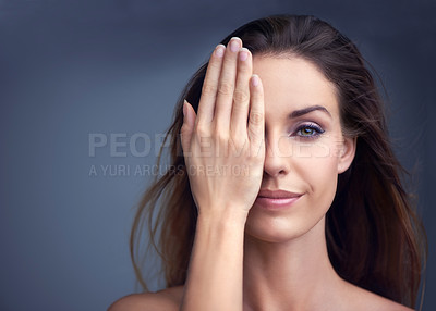 Buy stock photo Portrait of an attractive young woman covering half her face