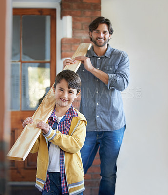 Buy stock photo A young boy helping his father with the home improvement