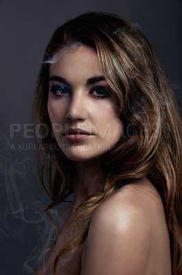 Buy stock photo concept shot of a beautiful young woman with smoke coming off her