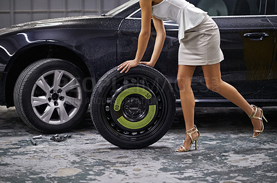 Buy stock photo Cropped image of a young woman wheeling a tyre