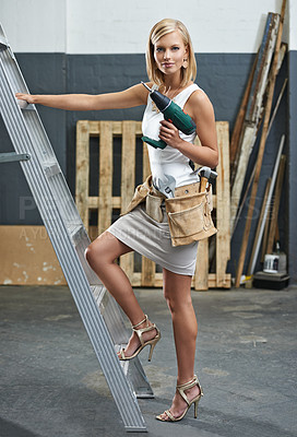 Buy stock photo A gorgeous young woman wearing a tool belt next to a ladder - conceptual