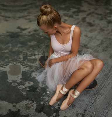 Buy stock photo A young ballerina sitting on a skateboard looking sideways
