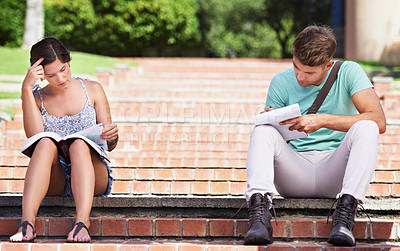Buy stock photo Cropped view of two young students studying on the steps in the park