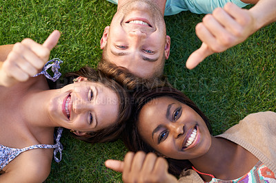 Buy stock photo A group of teenagers lying on grass showing a 'thumbs up' signal