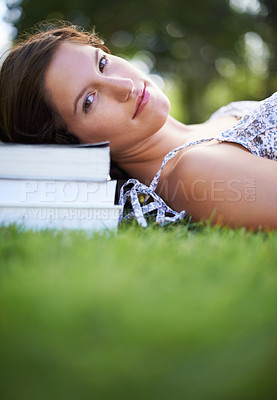 Buy stock photo A young woman lying in a park with her head resting on a pile of books