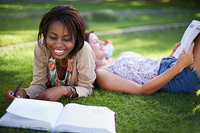 Buy stock photo Two young female students lying on the grass reading